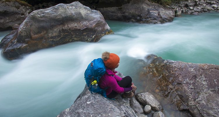 A woman takes a break from the trail and sits beside the Langtang Khola near the little village of Riverside on a misty evening, Langtang Region, Nepal, Asia