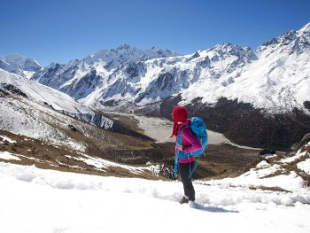 A girl surveys the Langtang valley from the top of Kyanjin Ri with the peak of Ganchempo far in the distance, Langtang Valley, Himalayas, Nepal, Asia