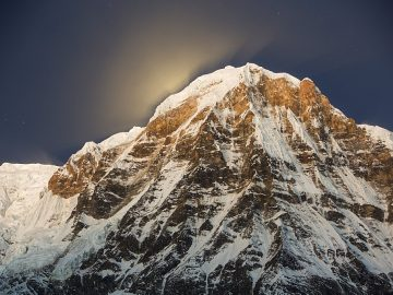 The night sky over Annapurna South in the Annapurna Sanctuary, with the glow from the setting moon behind the peak, Himalayas, Nepal, Asia